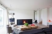 Loungebereich mit Kaminfeuer in modernem Ambiente, graue Sessel und Klassikerstuhl im Retro Look um rustikale Bodentische aus Vierkanthölzern