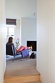 Blick durch schmalen Durchgang auf Chaiselongue mit Frau vor Kaminfeuer in modernem Ambiente