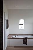 Eingebaute Badewanne mit dunkler Stein-Abdeckung unter Dachschräge, kleines Kippfenster