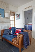 Brown leather sofa with blue and red scatter cushions and nautical accessories in living room with wood-effect wallpaper