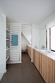 Modernes Bad, vor Fenster eingebautes Waschbecken mit Unterschränken und vertikaler Holzlatten Front, im Hintergrund weisser Handtuchtrockner an Schiebetürwand