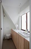 Platzsparendes Bad, vor Fenster eingebautes Waschbecken mit Unterschränken, vertikale Holzlatten Front, im Hintergrund Toilettte