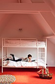 Boy reading on retro-style, white metal bunk beds on orange carpet in converted attic interior with exposed wooden beams