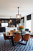 Wooden shell chairs with metal frames around dark dining table on retro rug with geometric patter in spacious interior with open-plan kitchen