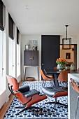 Klassiker Lounge Chair mit passendem Fussschemel auf Retro Teppich mit geometrischem Muster, im Hintergrund Essplatz in modernem Ambiente