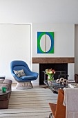 Pale blue classic armchair next to open fireplace below modern artwork in bright green, blue and white