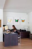 Frau mit Kind am Schreibtisch in Zimmernische, an Wand Bildergalerie mit buntem Schmetterlingmotiv