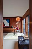Blick durch Türöffnung auf Schreibtisch und Kind in elegantem Arbeitszimmer mit Palisander vertäfelten Wänden und Klassiker Hängeleuchte