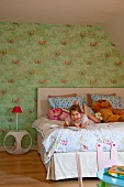 Girl reading on bed and table lamp on retro bedside table against green wallpaper with floral pattern