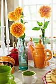 Gedeckter Tisch mit Apfelchips, Apfelkuchen, Blumenvasen und Teegeschirr