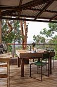 Old table and simple metal chairs wooden terrace