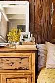 Flowers and mirrors on top of old cabinet next to bed