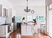 Woman and girl seating at country-house-style island counter below Rococo chandelier in open-plan kitchen