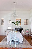 Chairs of various styles and Rococo chandelier in dining area in rustic interior