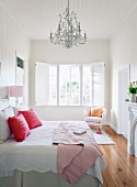 Double bed with pink scatter cushions on white bed linen below Rococo chandelier in white, wood-clad bedroom