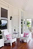 White wooden chairs with striped cushions on veranda of Colonial-style country house