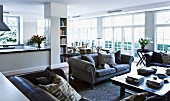 Traditional grey sofa and two leather sofas around coffee table in spacious, open-plan interior