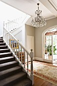 Open staircase, white carved wooden balustrade in grey-painted foyer of traditional country house