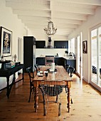 Various classic chairs around old wooden dining table in open-plan interior with modern black kitchen in background