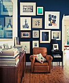 Brown leather armchair in corner of library with collection of pictures on blue-painted wall