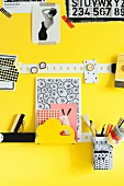 Metal strips and small magnets used as magnet pin board on yellow wall