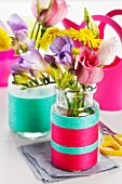 Small glass bottles wrapped in colourful woollen yarn used as vases