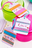 Small gift tags wrapped in colourful woollen yarn on plastic pots of different colours