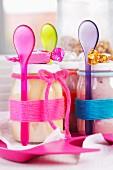 Joghurtgläser und Plastiklöffel mit farbigen Wollfäden umwickelt