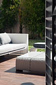 View through open door of modern, white wicker outdoor furniture on wooden terrace in summery atmosphere