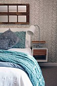 Light blue knitted blanket on bed with scatter cushions in various shades of blue and bedside cabinet with table lamp mounted on wall with grey and white wallpaper