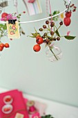 Sprigs of rose hips in tiny glass bottles hanging from white metal wreath