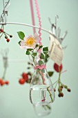Sprigs delicate wild roses in tiny glass bottles hanging from white metal wreath