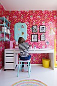 Girl sitting at desk in nostalgic bedroom; pink wallpaper with floral pattern