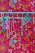 Necklaces of colourful beads hanging from hooks on pink, floral wallpaper