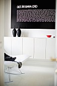 Partial view of modern rocking chair and black vessels on white, floating sideboard below black panel with white lettering