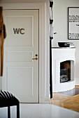 Ofener Eckkamin daneben weisse Zimmertür mit WC-Schild