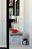 Stool with grey furry cover in front of mirror on wall