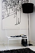 Delicate white Spaghetti Chair and black standard lamp in front of picture in corner