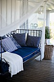 Metal day bed with white and blue cushions below canopy in front of small potted tree on wooden veranda floor