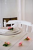 Roses and place setting on white wooden table and chair with name on backrest
