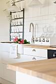 Ausschnitt einer weissen Landhausküche, Rosen in Spülbecken, an Wand Metall Flaschentrockner