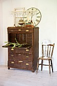 Vintage, dark wood bureau and chair against wall in rustic foyer