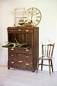 Vintage Sekretär aus dunklem Holz und Stuhl vor Wand in ländlichem Vorraum