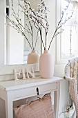 Vase of twigs and ornamental letters on white console table below framed mirror