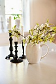 Branches of white blossom in china jug and candlesticks on white table