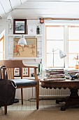 Books on antique wooden table in white, wood-clad room with rustic ambiance