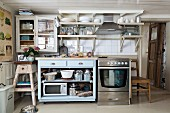 Rustic kitchen in mixture of styles; fifties-style base cabinet next to stainless steel cooker in rustic house
