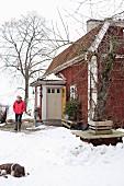 Frau und Hund in verschneitem Garten vor rotbraunem Holzhaus mit Windfang Eingang