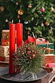 Hand-crafted, floating, spherical arrangement of fir twigs and red candles on metal dish in front of decorated Christmas tree