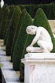 A stone figure on a plinth in the Garden of the Palace of Versailles